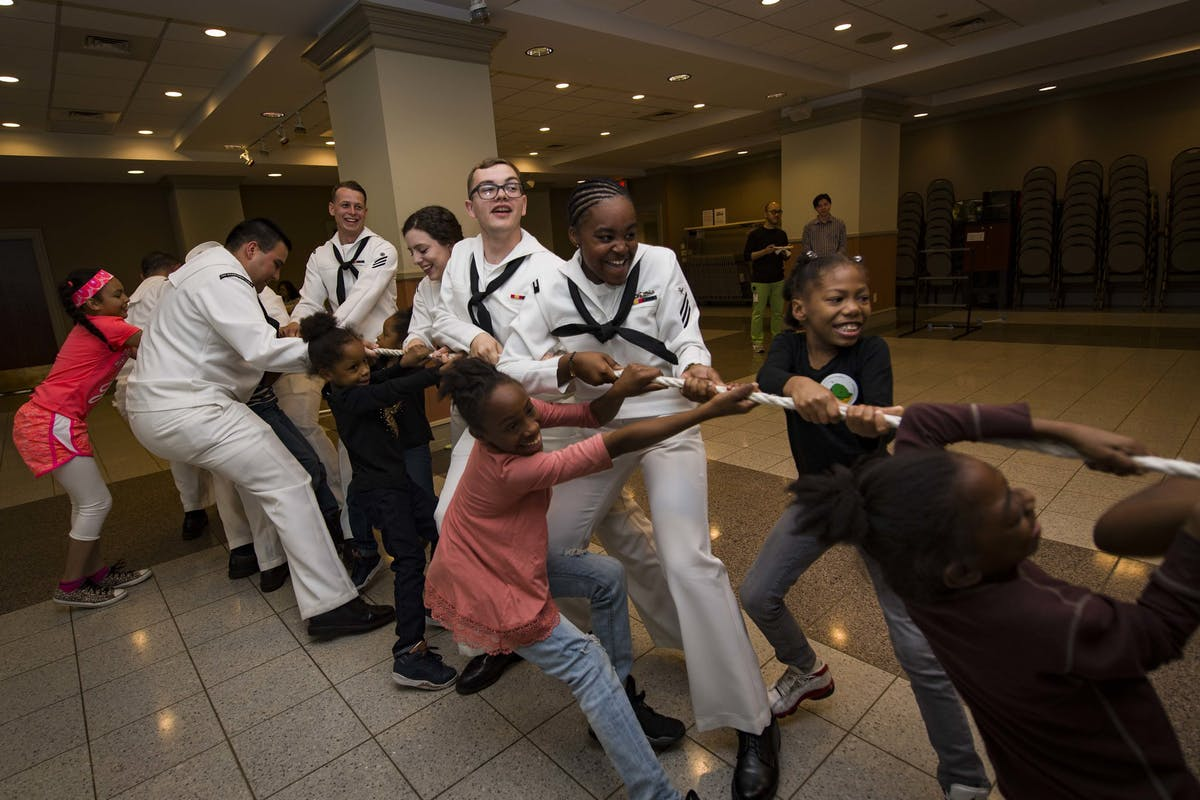 Sailors assigned to the amphibious assault ship USS Kearsarge (LHD 3) play tug of war with Project Hope children at the Times Square Church in downtown Manhattan for 2017 Fleet Week New York (FWNY).