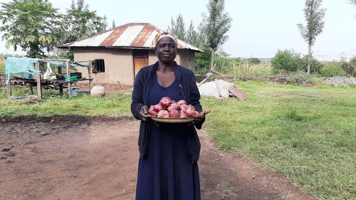 Eunice Outa with an onion harvest at her farm in Nyakach