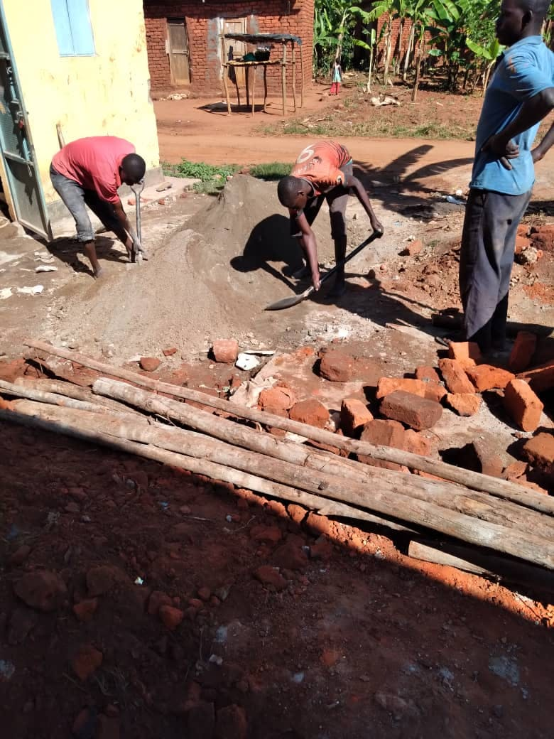 Mukhwana and his team mixing material for the construction of a new biogas pit at a rural home in Mbale district.