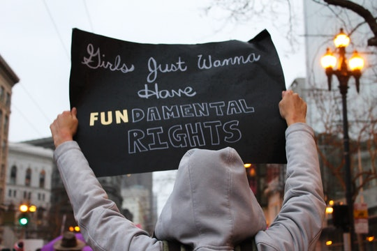 woman holding a sign that says girls just wanna have fundamental rights