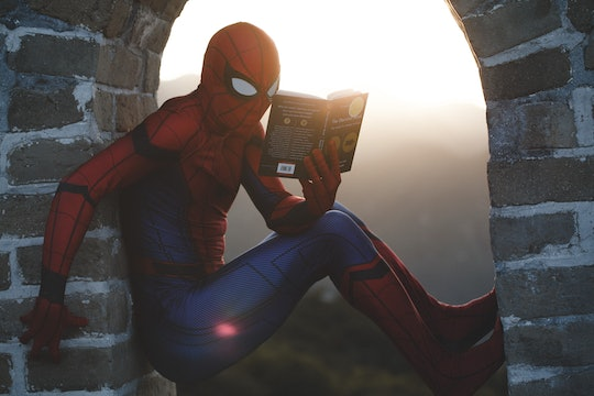 A person wearing a Spiderman costume sits in an open window reading a book.