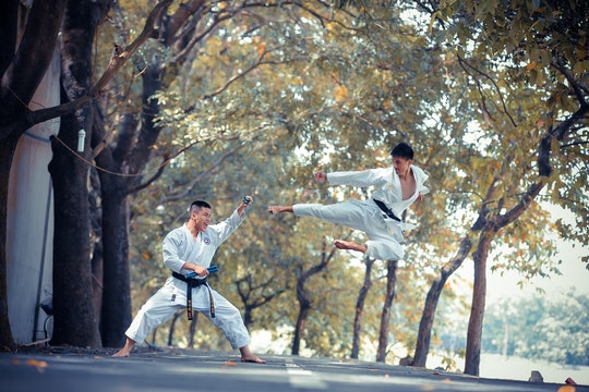 Two men performing martial arts. One is doing a flying kick towards the other.