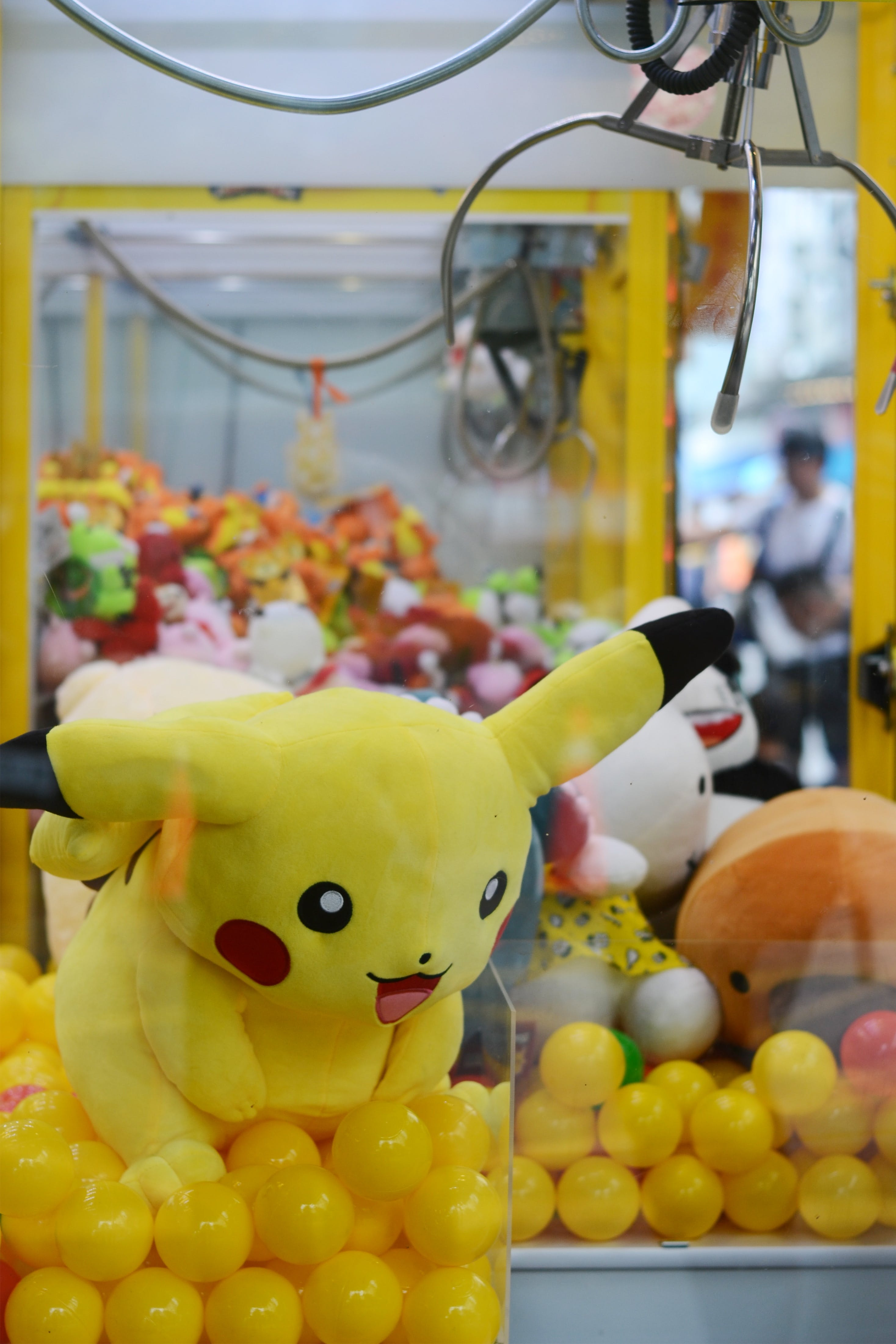 A claw machine with full of toys including a large pikachu from the Pokemon series