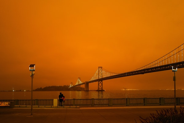 A couple looks out on the Golden Gate Bridge with an orange sky from California wildfires, September 2020