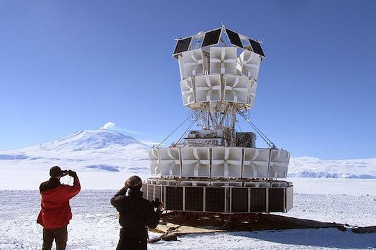 two people looking at a giant white ballon structure in antarctica