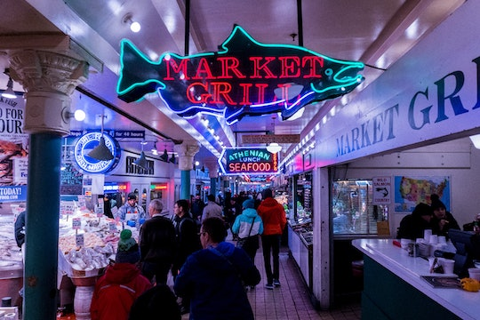 """A crowd of people at the Seattle Public Market, in front of a sign that says """"Market Grill."""""""
