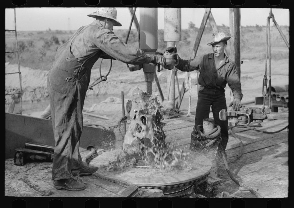 black and white photo of two oil workers working on a pipe with oil spilling from it