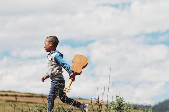 A boy walking with a ukulele.