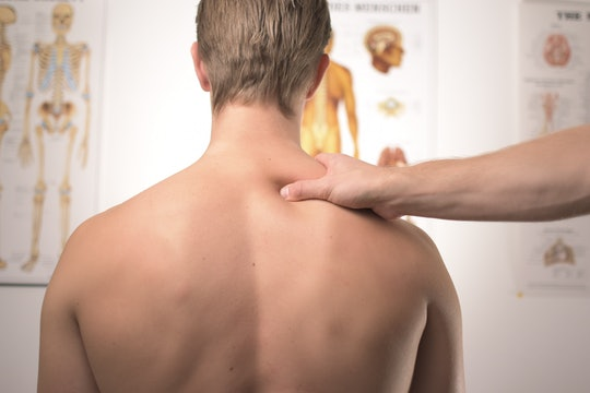 A man in a doctor's office with neck and shoulder pain