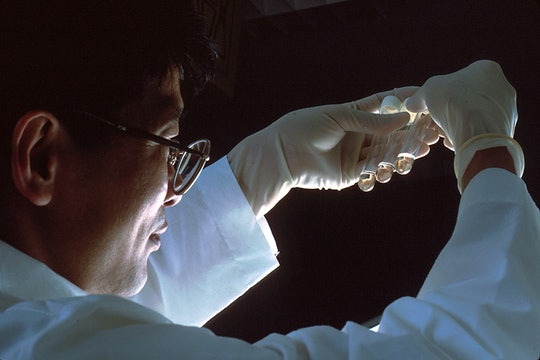 A scientist wearing a white lab coat and latex gloves holds three test tubes with clear liquid in them up to the light.