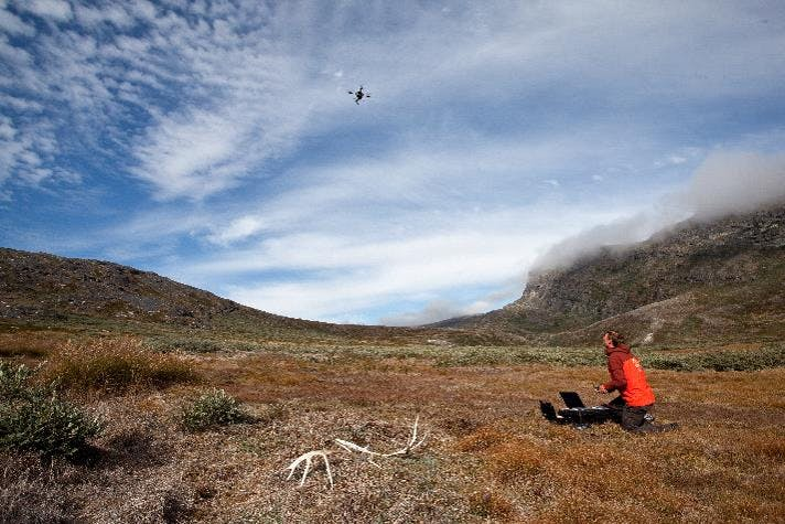 In a grassy valley, a scientist kneels and pilots a drone, flying against a cloudy sky.