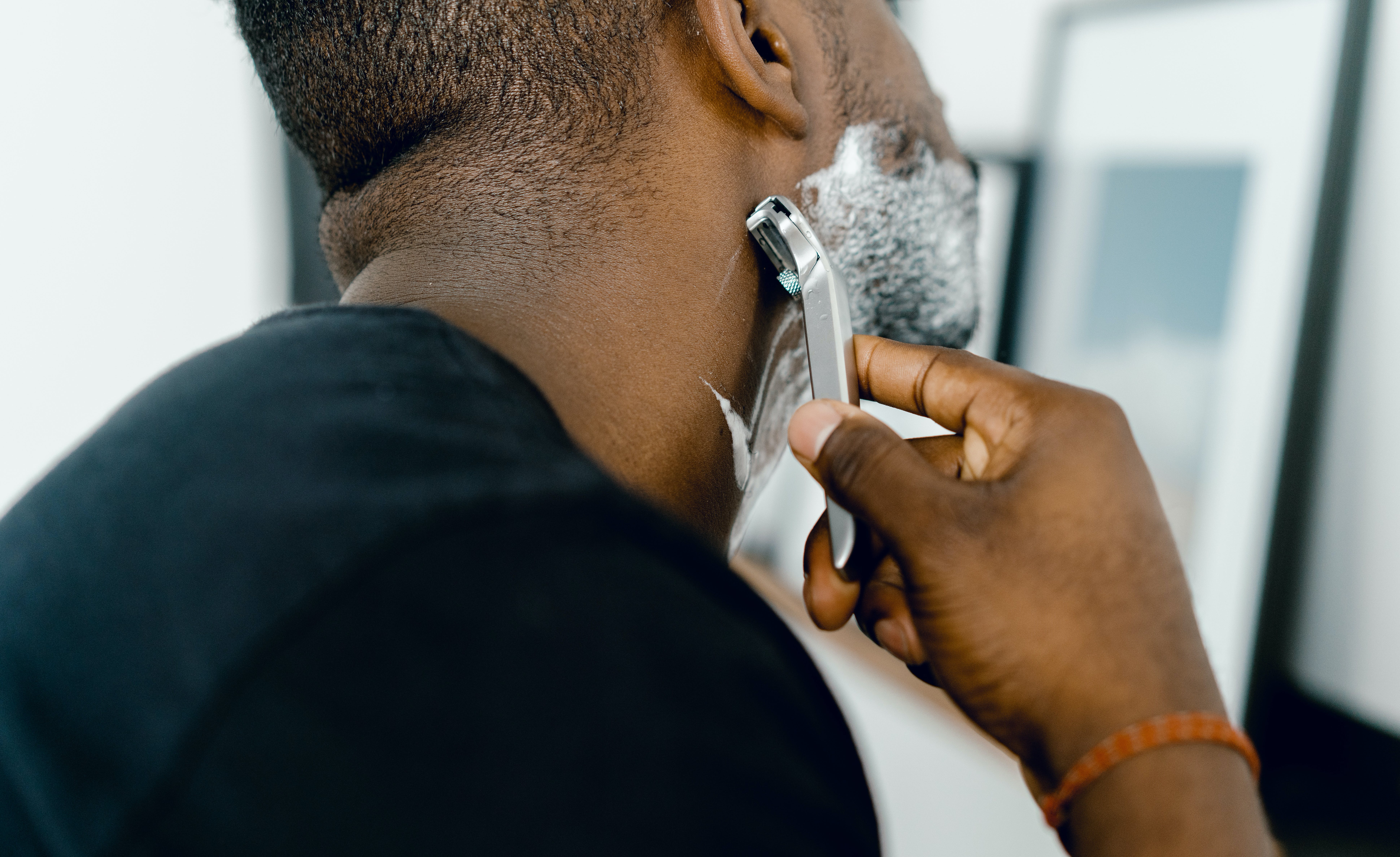 A man shaves himself with shaving cream and a razor.