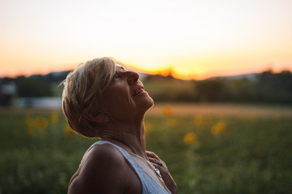 a woman looking up at the sky smiling slightly