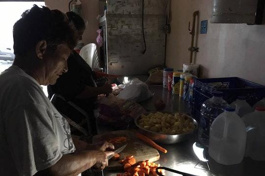 A older woman prepares dinner in a dark kitchen in Puerto Rico.