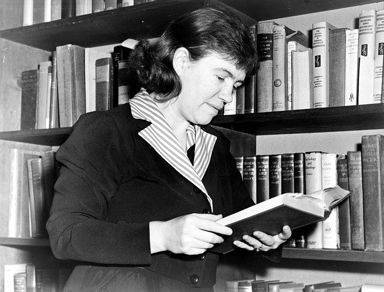 black and white photo of mead reading a book in her office