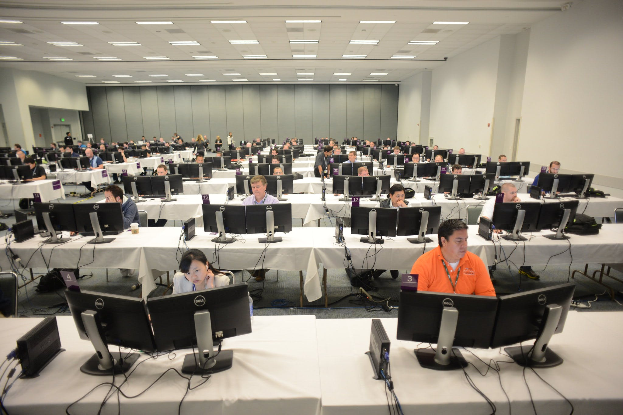 A computer lab filled with computers, with people sitting at them working.