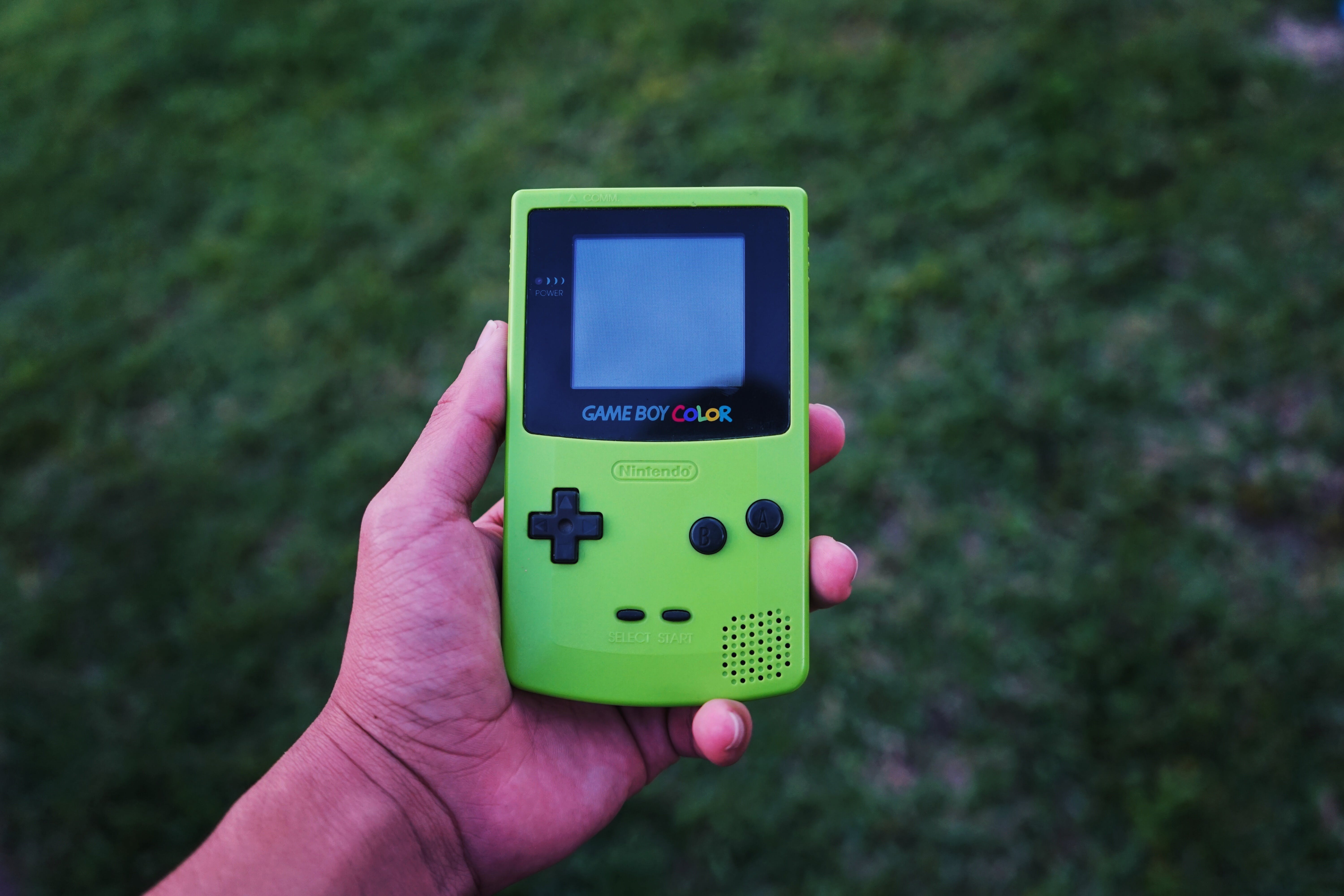 A person holding a green Game Boy Color in their hand