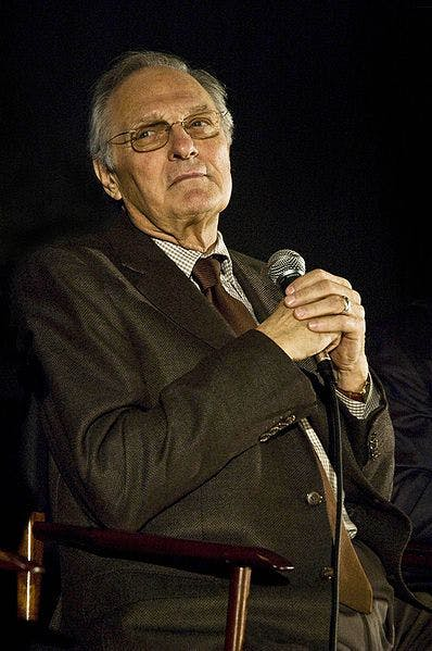 actor alan alda holding a microphone