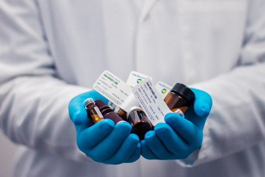 White coat with gloves holding drugs
