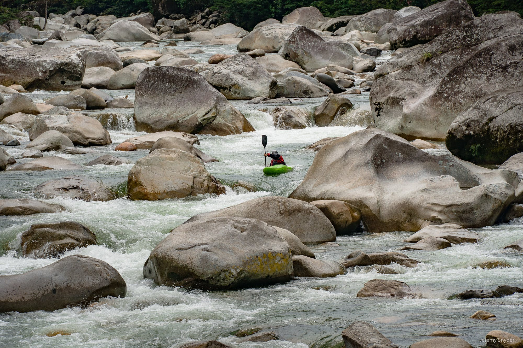 A kayaker paddles the Piatua river in Ecuador, among boulders brought down from the Andes