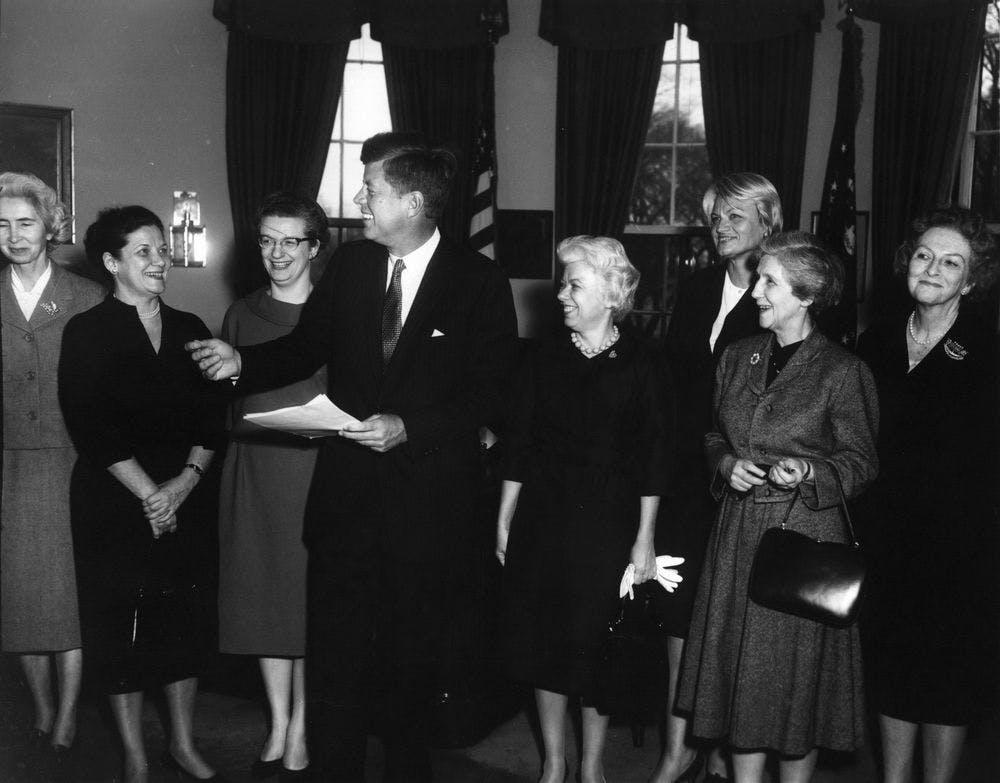 Nancy Grace Roman standing next to President John F. Kennedy, receiving 1962 Federal Woman's Award