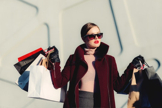 A woman wearing sunglasses holding a bunch of shopping bags.