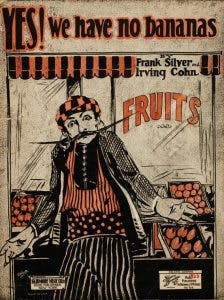 "Cover of sheet music for ""YES! We have no bananas,"" showing a man with a long mustache shrugging in front of a grocery display of fruit"