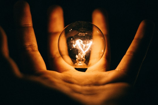 a hand holding a lightbulb in the dark