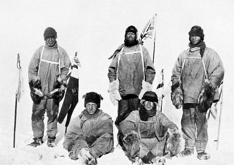 five men in a black and white photograph taken in Antarctica