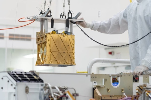 Technicians at NASA's Jet Propulsion Laboratory lower the Mars Oxygen In-Situ Resource Utilization Experiment (MOXIE) instrument into the belly of the Perseverance rover.