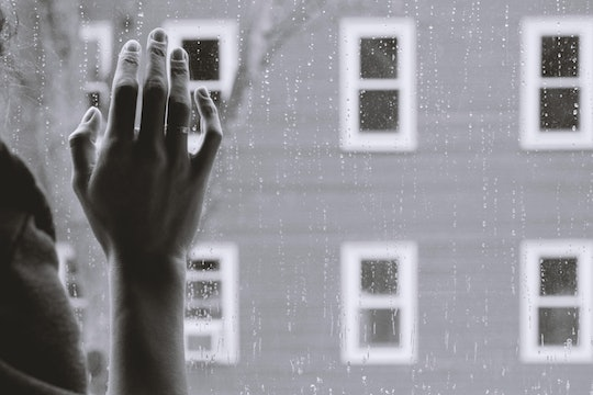 hand on window person looking outside