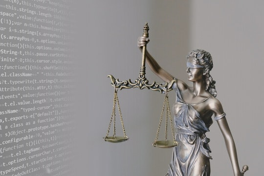 """Figurine of """"blind justice"""" with computer code in the background"""