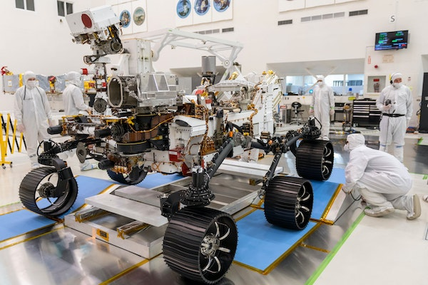 a mars rover being worked on in a lab by scientists in white clean suits