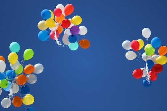 Colorful balloons released into a blue sky.
