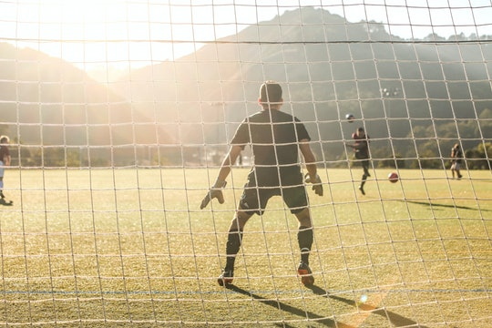 picture of a soccer goalie from behind the net during the daytime
