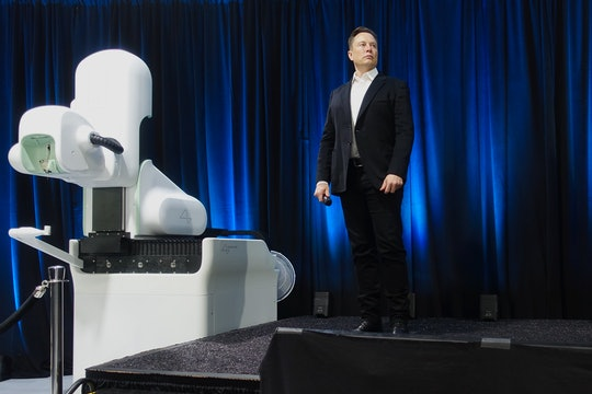 Elon Musk stands on stage next to a Neuralink device