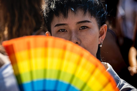 A person looks out from behind a rainbow-colored fan.