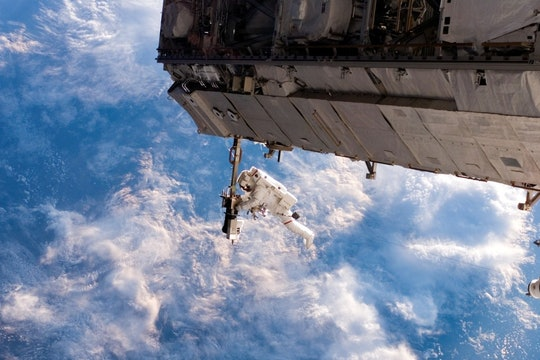 astronaut working on the international space station against a backdrop of clouds