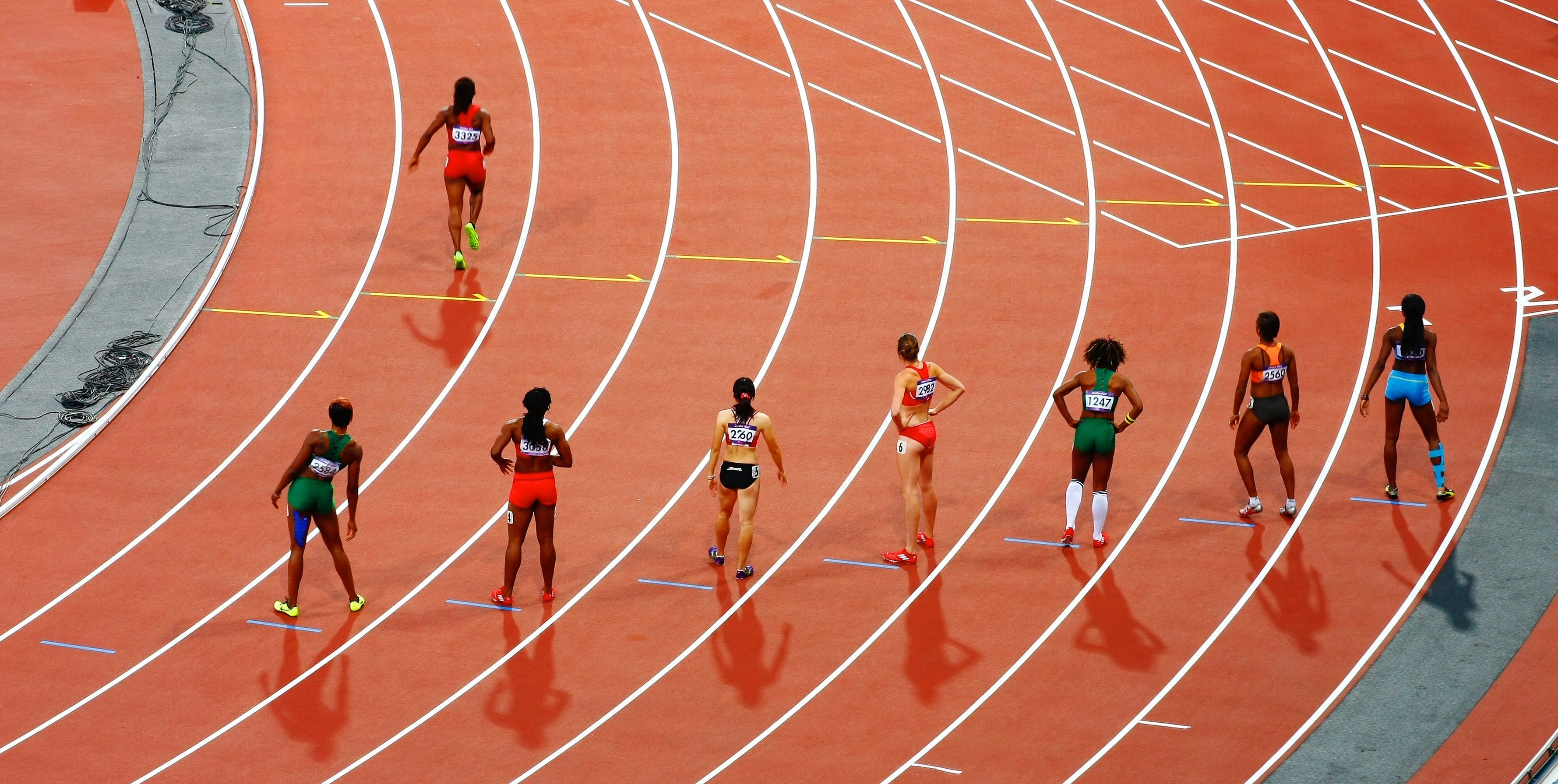 A photo of sprinters on a track waiting at the starting line.