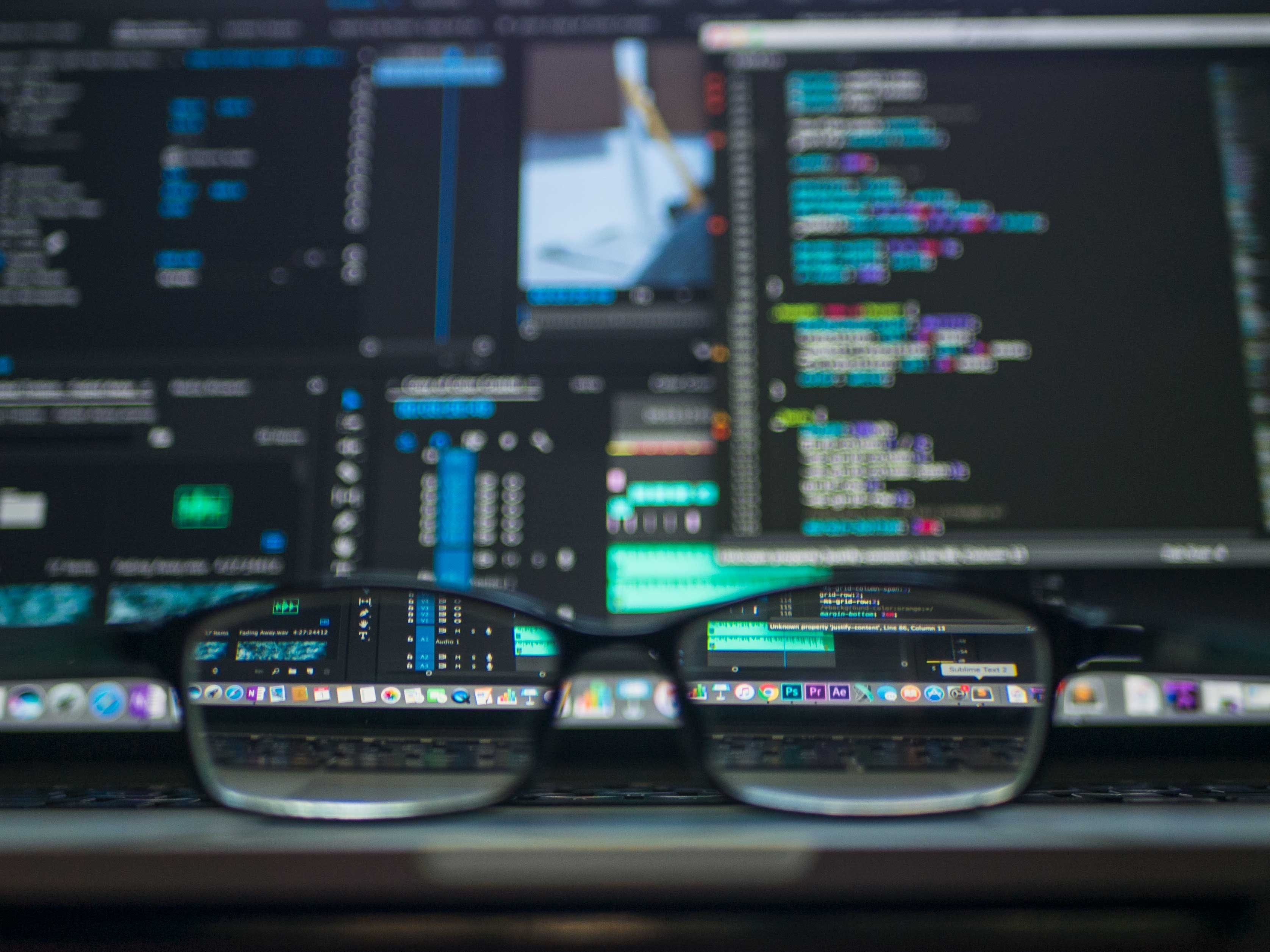 A blurry screen with computer code on it. Looking through the lens of a pair of glasses makes the code easy to read.
