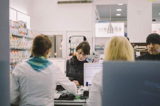 A woman completes a purchase at a pharmacy