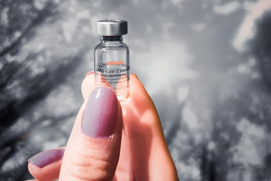 a woman's hand holding a vial of vaccine against a sky backdrop