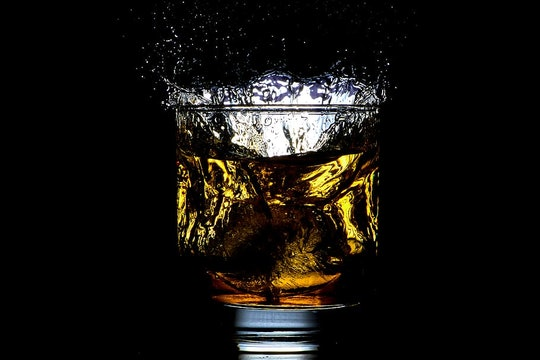 glass of liquid against a black background