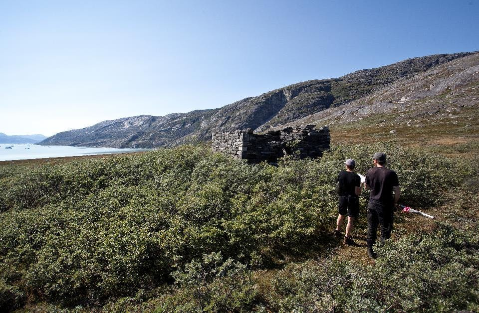 Two scientists surveying the ruins of a stone house in Greenland.