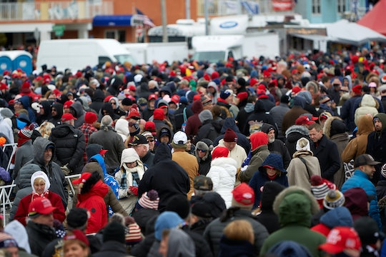 A crowd of people, many of which have red baseball caps.