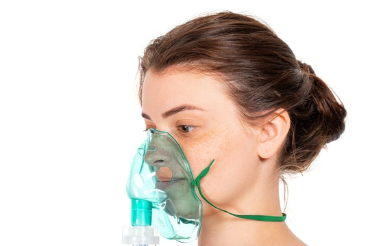 a woman wearing a green oxygen mask