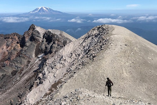 person hiking along the crater of the mountain