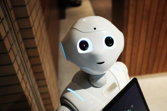 A white robot looks up towards the camera.