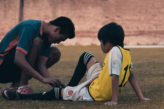 two young soccer players, one with an injury and one helping him