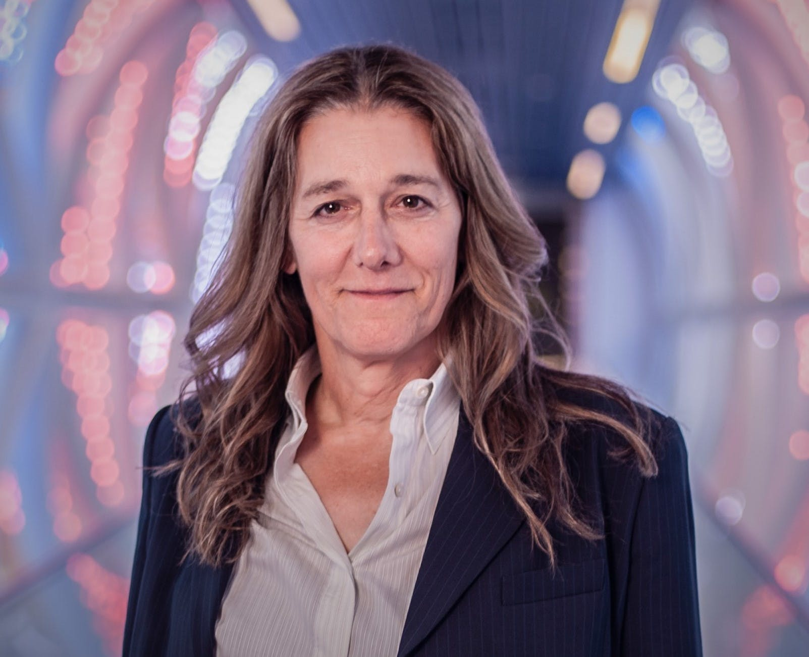 A headshot of Martine Rothblatt, a woman with shoulder-length brown hair, wearing a white shirt and a navy jacket.